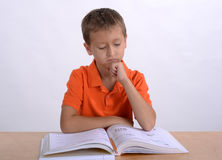 Boy reading homework. At the desk Stock Photography