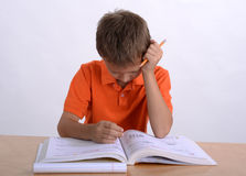 Boy reading homework. And holding his head Royalty Free Stock Photos