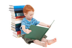 Boy reading kids book and leaning on stacked books