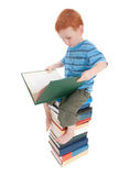 Boy reading kids book on pile of books Stock Image