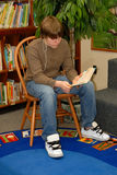 Boy Reading in Library. A teen boy listens to tunes while reading in library Stock Image