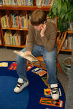 Boy Reading in Library. A teen boy listens to music while reading in library Royalty Free Stock Image