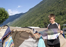 Boy reading map at tent. A teenage boy reading a map, standing next to a tent. The Alps in the background royalty free stock photos