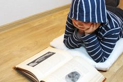 Boy is reading an old book Stock Photography