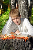 Boy reading outdoor. Teenage boy sit in autumn forest with a book Stock Photography