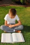 Boy Reading Outside Stock Photo