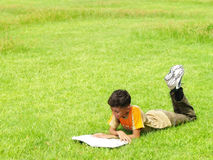 Boy reading outside. A boy lies in the grass reading Stock Image