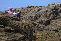 Boy reading between the rocks royalty free stock image