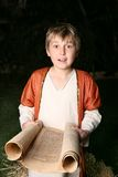 Boy reading a scroll stock photo