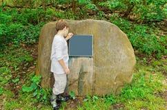 Boy reading sign on boulder Stock Image