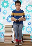 Boy reading and sitting on book tower in front of cog gear settings. Digital composite of Boy reading and sitting on book tower in front of cog gear settings Royalty Free Stock Photography