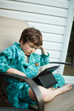 Boy reading on a tablet. Outside in pajamas Royalty Free Stock Photo