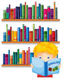 A boy reading with a wooden shelves at the back Stock Images