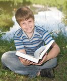 Boy reads a big book Royalty Free Stock Image