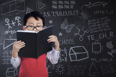 Boy reads book in class while standing. Cute little boy wearing glasses and standing in the classroom while reading a book with doodles on the chalkboard Stock Image