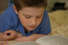 Boy reading a book lying on the bed royalty free stock photos