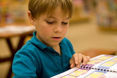 Boy reads a book at libary. A 7 year old boy reads a book at the library or book store.  He has light brown hair and wears a turquoise polo shirt Royalty Free Stock Photos