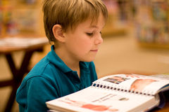 Boy reads a book at libary. A 7 year old boy reads a book at the library or book store.  He has light brown hair and wears a turquoise polo shirt Stock Photo