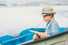 Boy reads a book in old boat on the lake bank Stock Photo