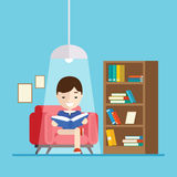 Boy reads a book while sitting on the couch Royalty Free Stock Photos