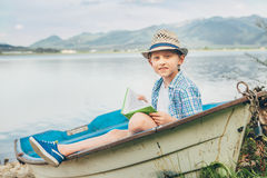 Boy reads a book sitting in old boat on the lake bank Royalty Free Stock Images