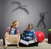 Boy reads a book to his little sister Royalty Free Stock Photography