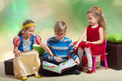Boy reads a book to little girls Royalty Free Stock Photos