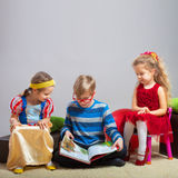 Boy reads a book to little girls Royalty Free Stock Photography
