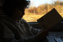 Boy reads a book on train journey Stock Image