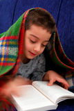 Boy reads book under blanket Stock Image