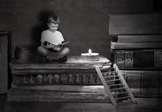 The boy is sitting on big books. A wooden staircase leads to a pile of books royalty free stock photo