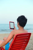 Boy reads the ebook on the sea shore Royalty Free Stock Photography