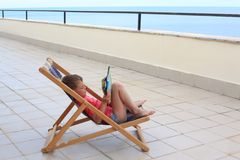 Boy reads in lounge on veranda stock image
