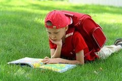 The boy reads the textbook sitting on a grass Royalty Free Stock Images