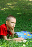 The boy reads the textbook sitting on a grass Stock Image