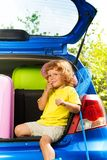 Boy ready for car trip. Nice little 3 years old boy sitting in the trunk of the car with finger on the mouse dreaming and thinking about trip Stock Image