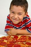 Boy ready to eat a pizza. A handsome young smiling boy ready to eat a pepperoni and sausage pizza stock photos
