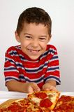 Boy ready to eat a pizza. A handsome young smiling boy ready to eat a pepperoni and sausage pizza stock image