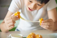 Boy ready to eat sticky stretch fried cheese ball royalty free stock image