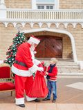 Boy Receiving Gift From Santa Claus Stock Photos