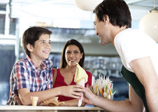 Boy Receiving Vanilla Ice Cream Cone From Waiter By Mother Royalty Free Stock Photography
