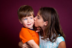 Boy Recoils From His Older Sister Who Is Kissing Him Royalty Free Stock Image