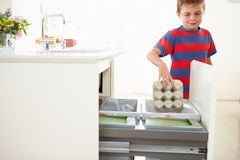 Boy Recycling Kitchen Waste In Bin. Wearing Striped Top Royalty Free Stock Photography
