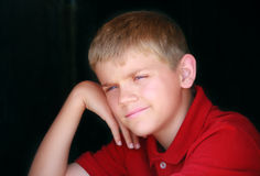 Boy in Red. Cute boy in red shirt with hand on his cheek, puzzled expression Stock Photo