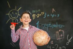 A boy with a red airplane and a globe stands on the background of a school board stock image