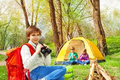Boy with red backpack holding black binocular Stock Photography