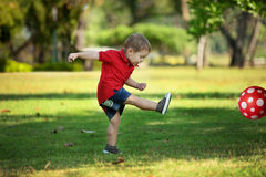 Boy with Red Ball. Infant boy in red shirt kicking red football out of frame in park Stock Photography