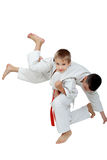 A boy with a red belt doing throw athlete with a white belt. A boy with a red belt doing throw athlete Royalty Free Stock Images