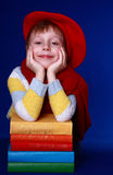 Boy in red beret with colorful books. Blond little boy in read beret and scarf sitting with a pile of colorful books on blue background Stock Image