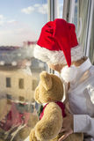 A boy in a red cap looks out the window. He is holding a teddy bear. Boy in white shirt Stock Images